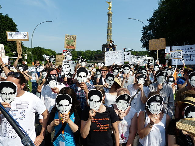A landscape photo of a protest in Germany, where several people are wearing Chelsea Manning and Edward Snowden masks.